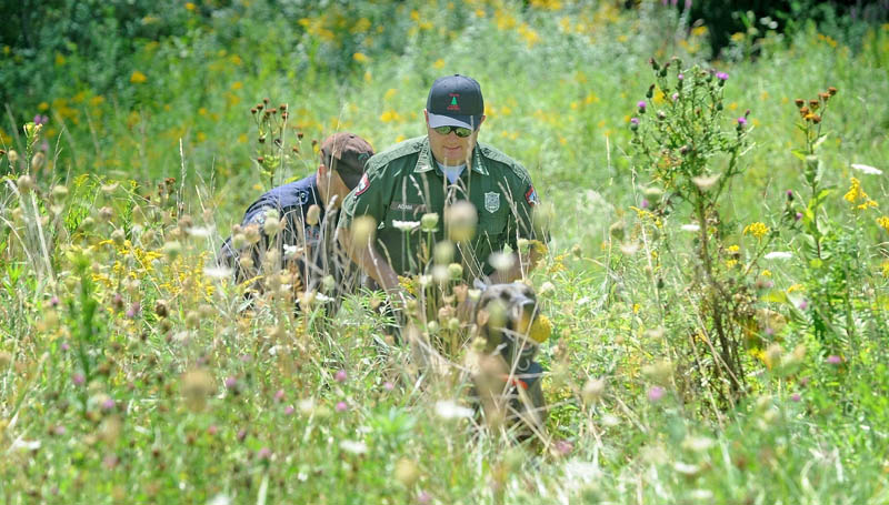 Lt. Kevin Adams, foreground, of the Maine Warden Service, state police Trooper Shawn Porter and search dog Myka emerge from the woods near Skowhegan's Reddington-Fairveiw General Hospital on Fairview Avenue shortly after finding the body of Vaughn Giggey III on Tuesday.
