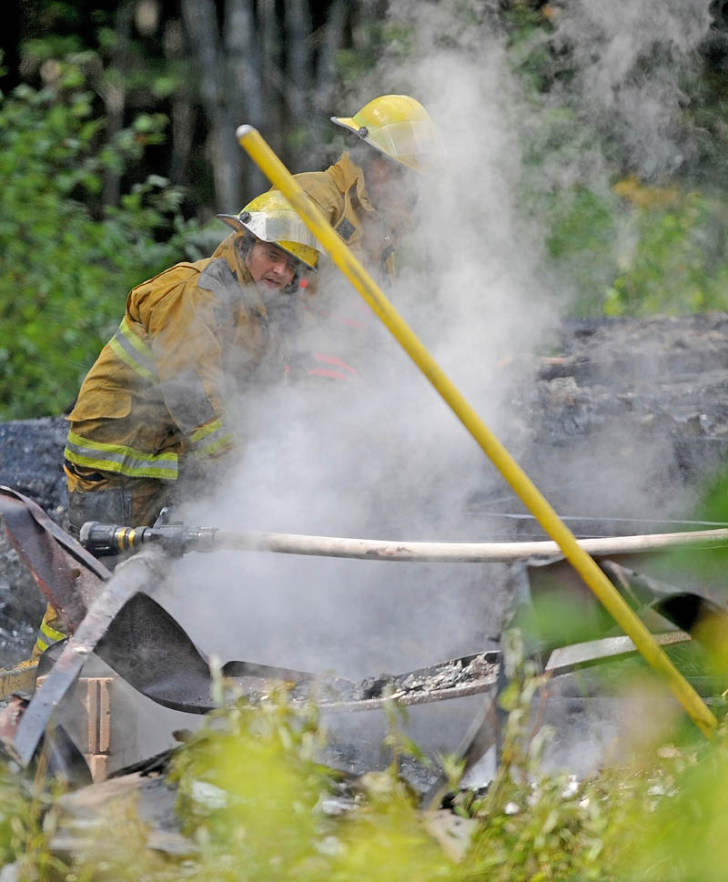 Firefighters from Burnham and Unity mop up a mobile home fire on Pond Road in Burnham today.