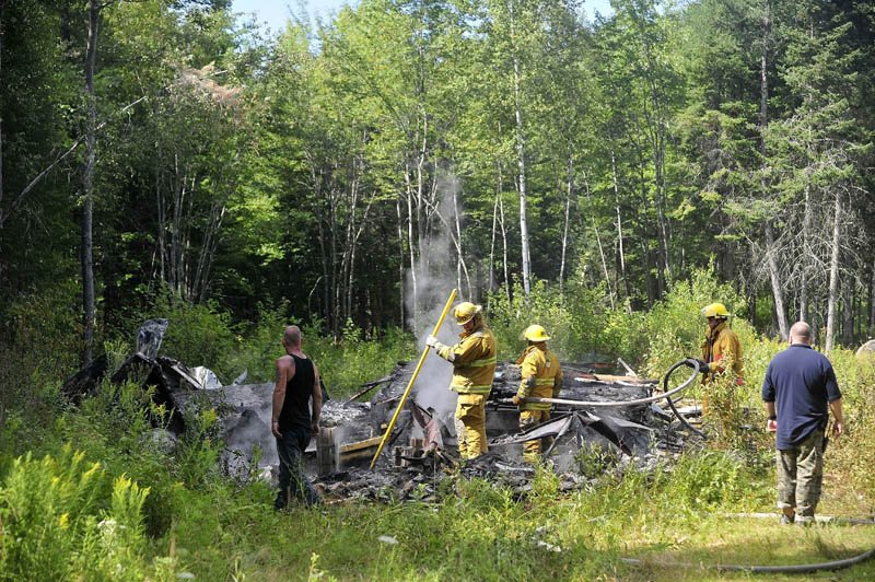 Firefighters from Burnham and Unity mop up a mobile home fire on Pond Road in Burnham today. The structure was destroyed. Firefighters from Troy and Pittsfield were also on scene.