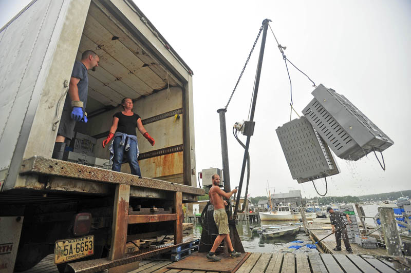 Heidi Simmons, center, stands inside the transport truck as Craig Mott, 36, right, dock manager at the Friendship Lobster Co-op in Friendship Harbor, helps load crated lobsters onto a truck bound for a sorting facility in the town of Bremen on July 29.