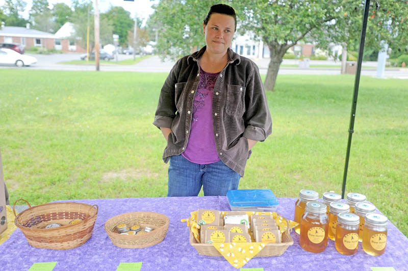 Samantha Burns, owner of Runamuk Acres in Anson, stands by some of her bee-friendly products at the Madison farmers market at a new park on Main Street today.