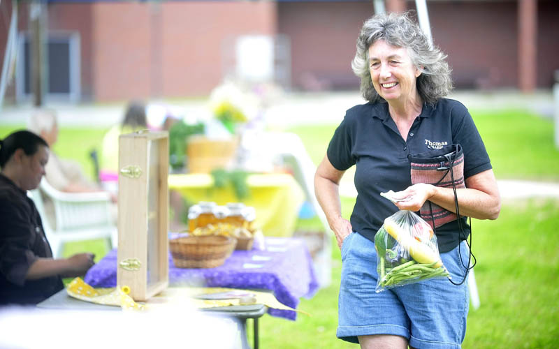 Ellen McQuiston, of Anson, shops at the Madison farmers market at a new park on Main Street today. The farmers market will be open on Sundays from 9 a.m. to 2 p.m. through Sept. 8.