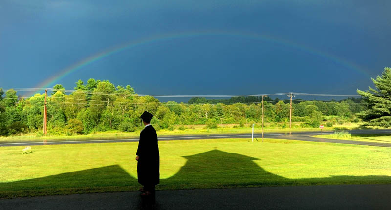 Cody Buzzell, 17, stands in the shadow of Moody Chapel as a rainbow shines over Hinckley, before the Maine Academy of Natural Sciences' inaugural commencement today.