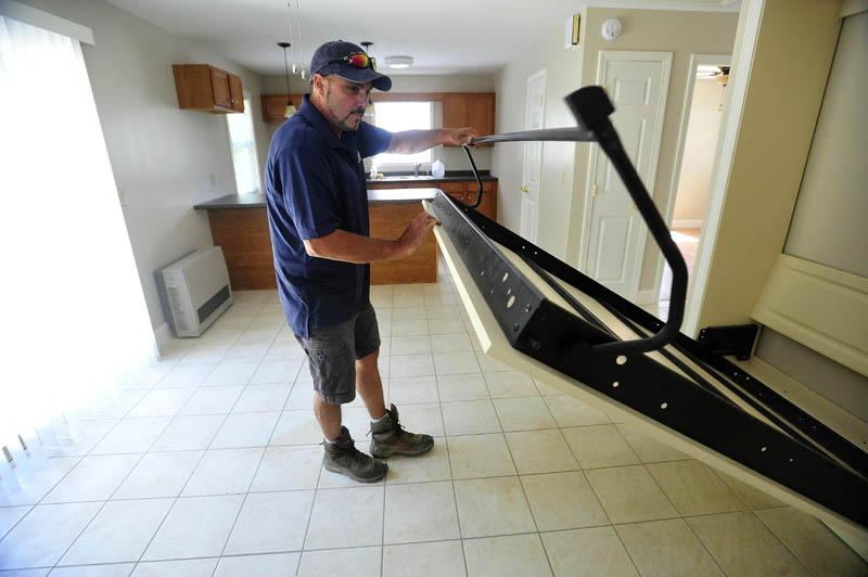 Andy Vear, a local real estate developer, shows the Murphy pull -out bed for guests in the combined kitchen, dining and living area at his 20 Cool St. microhome in Waterville on Tuesday. The main bedroom is behind the door to the right, and next to that is a full bathroom.