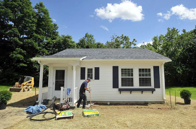 Sam Tieman landscapes the front of the newly built microhome at 20 Cool St. in Waterville on Tuesday. The energy-efficient dwelling has one bedroom and a full bathroom, complete with washer and dryer hook-ups. The building's total utilities cost for a year is estimated at $400.