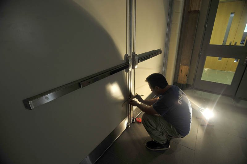 Jesse Donovan, from Donovan Co., installs doors in the new hallway at the entrance of Mt. Blue Learning Campus in Farmington today.