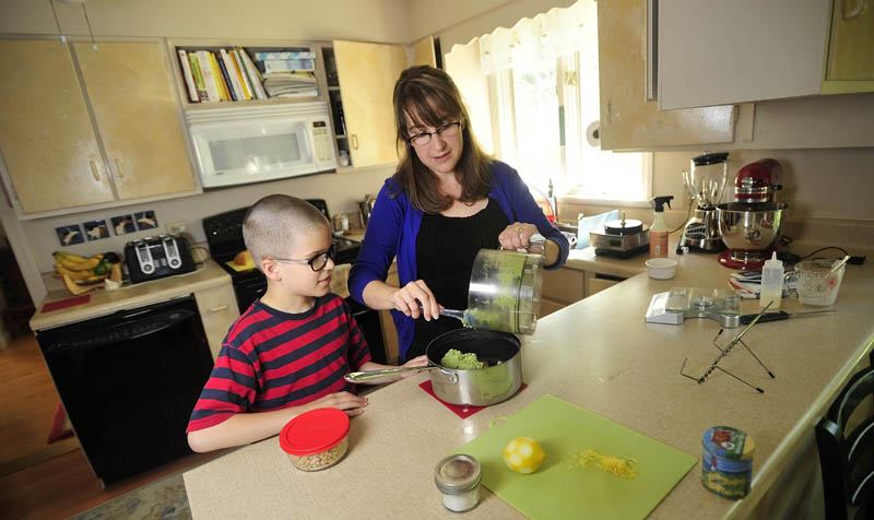 Noah Koch, 9, and his mother, Hilary, of Waterville, prepare his award-winning pesto in their Waterville home today. Noah was selected as a winner in First Lady Michelle Obama's Healthy Lunchtime Challenge.