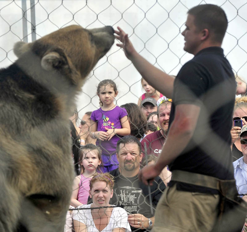 Dexter Osborn, owner of A Grizzly Experience, puts on a show with his grizzly bear, Tonk, at the Skowhegan State Fair today.