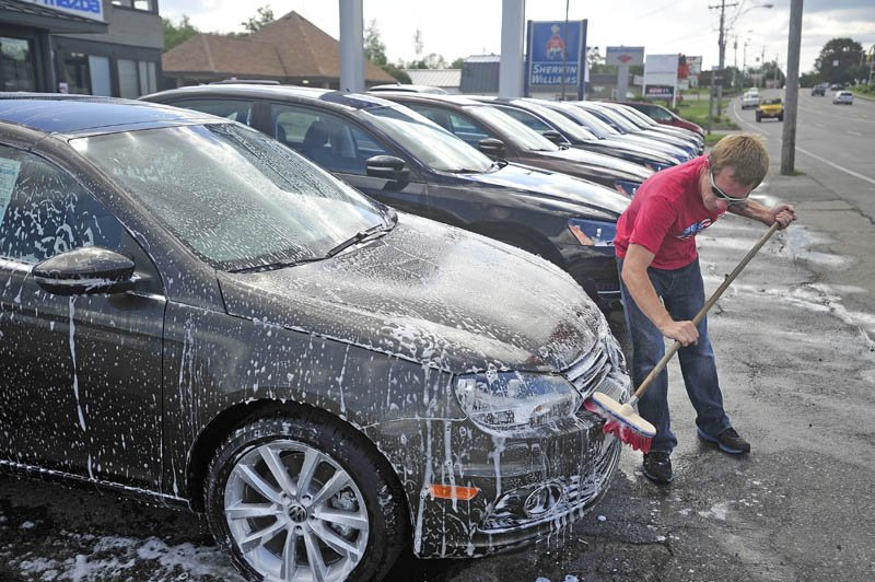 Dominic Frost, 31, washes one of the estimated 125 cars on the lot at Thompsons Audi / Volkswagon on Main Street in Waterville today. The weather and a second set of hands from helper Sander Spensson moved the process along rather quickly.