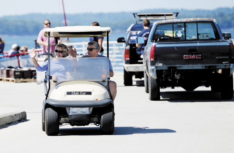 Camille and Wes Wolfertz, of Long Island, wave as they drive their golf cart from the dock at Long Island after a trip to the main land for supplies Thursday.