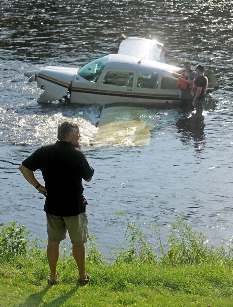 Ray Ayer, 59, of Monmouth, stands on the banks of the Kennebec River as crews try to secure a cable to a disabled airplane he piloted, after it crashed into the Kennebec River in Bingham today.