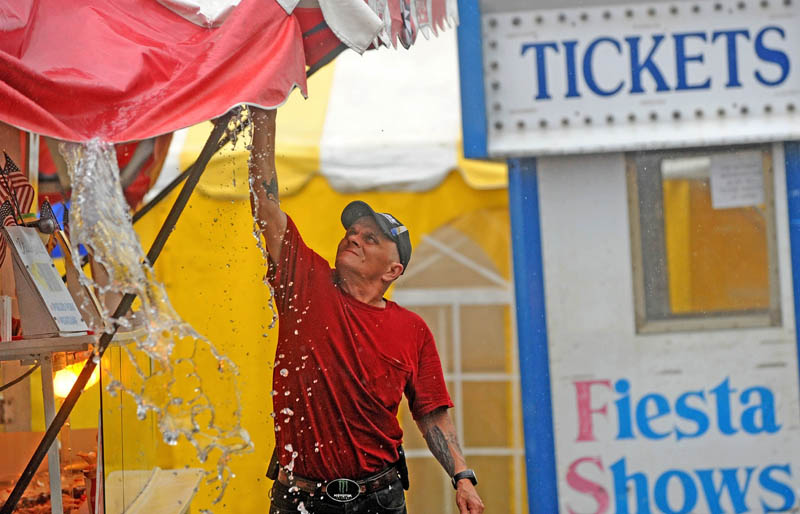 Staff photo by Michael G. Seamans Eddie Cote, a worker with Andrew's Concessions, clears the tents of standing waters rain falls on the 195th annual Skowhegan State Fair at the Skowhegan Fairgrounds on Friday.