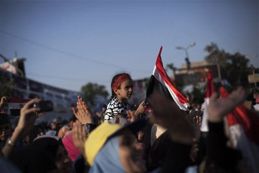 An Egyptian girl waves a national flag while supporters of Egypt's ousted President Mohammed Morsi chant slogans against the Egyptian Army at the sit-in at Rabaah al-Adawiya mosque, which is fortified with multiple walls of bricks, tires, metal barricades and sandbags, and where protesters have installed their camp in Nasr City, Cairo, Egypt, on Sunday.