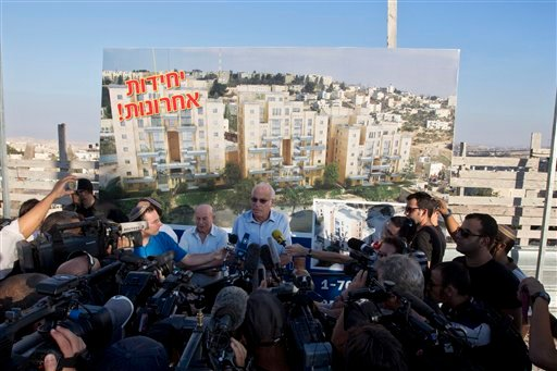 """Israeli Minister of Housing and Construction Uri Ariel, center, speaks to journalists during a ceremony to mark the resumption of the construction of housing units in an east Jerusalem neighborhoodtoday. Israel's housing minister today gave final approval to build nearly 1,200 apartments in Jewish settlements, just three days before Israeli-Palestinian peace talks are to resume in Jerusalem. Hebrew on the sign reads """"Last Units."""""""