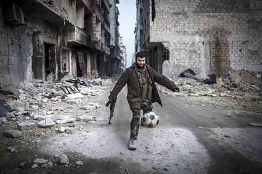 In this Jan. 2 file photo, a Syrian rebel plays soccer in the Saif al-Dawlah neighborhood of Aleppo, Syria. For Syria's banned Muslim Brotherhood, the uprising against President Bashar Assad that erupted amid Arab Spring revolts in 2011 provided a long-sought opportunity to stage a comeback after decades spent in exile.