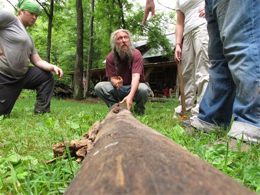 "Eustace Conway, center, shows campers how to split a log at his Turtle Island Preserve in Triplett, N.C., on June 27. When Conway bought his first 107 acres in 1987, his vision for Turtle Island was as ""a tiny bowl in the earth, intact and natural, surrounded by pavement and highways."" People peering inside from nearby ridges would see ""a pristine and green example of what the whole world once looked like."""