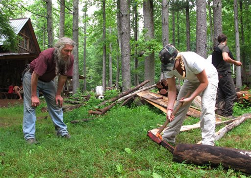 Eustace Conway, left, offers encouragement as a camper hammers a wedge into a log at his Turtle Island Preserve in Triplett, N.C., on June 27. People come from all over the world to learn natural living and how to go off-grid, but local officials ordered the place closed over health and safety concerns.