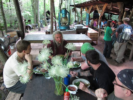 Naturalist Eustace Conway, center, speaks to diners at the Nacho Mama's eating hall at Turtle Island Preserve in Triplett, N.C., on June 27. People come from all over the world to learn natural living and how to go off-grid, but local officials ordered the place closed over health and safety concerns.