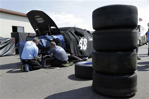 Crew members work on NASCAR Sprint Cup series driver Jimmie Johnson's main car during practice for the Pure Michigan 400 auto race at Michigan International Speedway in Brooklyn, Mich., Saturday, Aug. 17, 2013. Johnson crashed his primary car during practice. (AP Photo/Paul Sancya)