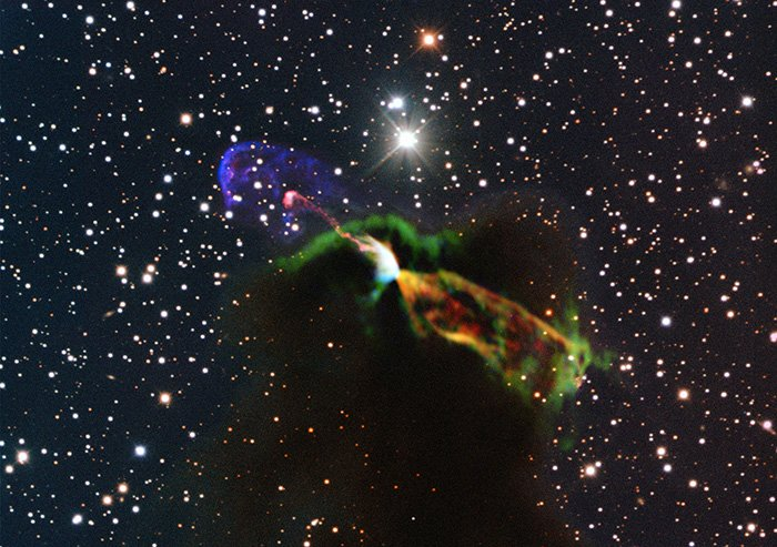 This image made available by the European Southern Observatory using radio and visible light frequencies shows the Herbig-Haro object HH 46/47. The orange and green, lower right, reveal a large energetic jet moving away from the Earth. To the left, in pink and purple, another jet is seen, streaming partly toward the Earth.