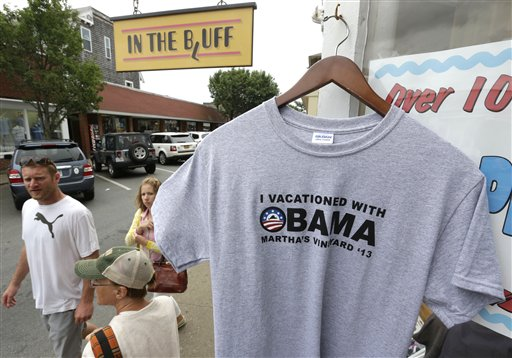 Passers-by walk past a souvenir T-shirt with President Barack Obama's name, right, at a shop in Oak Bluffs, Mass., on the island of Martha's Vineyard, on Friday. The first summer vacation of President Obama's second term is bringing him back to Martha's Vineyard, the well-heeled Massachusetts island.