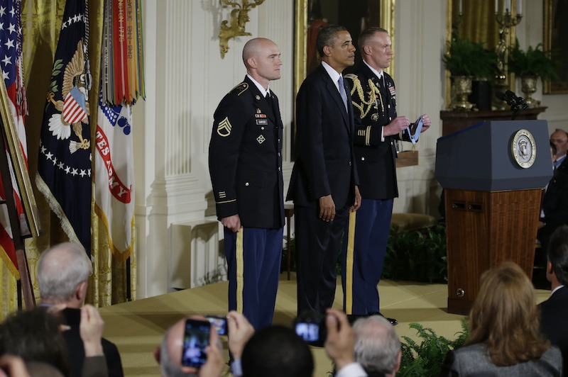 President Barack Obama stands with US Army Staff Sgt. Ty M. Carter as the citation is read as he awards him the Medal of Honor for conspicuous gallantry, Monday, Aug. 26, 2013, during a ceremony in the East Room of the White House in Washington. Carter received the medal for his courageous actions while serving as a cavalry scout with Bravo Troop, 3rd Squadron, 61st Cavalry Regiment, 4th Brigade Combat Team, 4th Infantry Division, during combat operations in Kamdesh District, Nuristan Province, Afghanistan on Oct. 3, 2009. Carter is the fifth living recipient to be awarded the Medal of Honor for actions in Iraq or Afghanistan. (AP Photo/Carolyn Kaster)