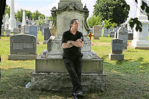 """Patric Abedin, who also goes by the name """"Nick Beef,"""" poses for a photo among the grave markers at Calvary Cemetery in the Queens borough of New York on Aug. 2. In 1975, Abedin bought the grave plot next to where presidential assassin Lee Harvey Oswald is buried, and then placed the granite marker inscribed with """"Nick Beef"""" there in 1997. For years, curiosity seekers visiting Oswald's Fort Worth, Texas, grave have wondered about the simple headstone next door."""