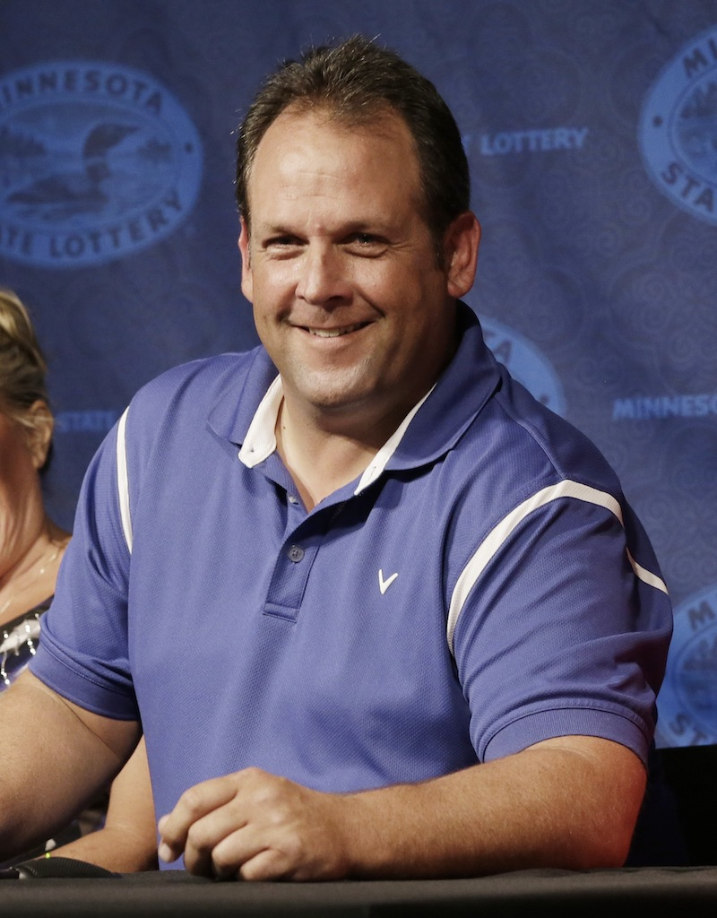 Paul White, of Ham Lake, Minn. has reason to smile after he was announced as one of the winners of the $448.4 million Powerball Jackpot, Thursday, Aug. 8, 2013 in Minneapolis. White's share of the jackpot is $149.4 million. The woman at left is a co-worker friend. (AP Photo/Jim Mone)