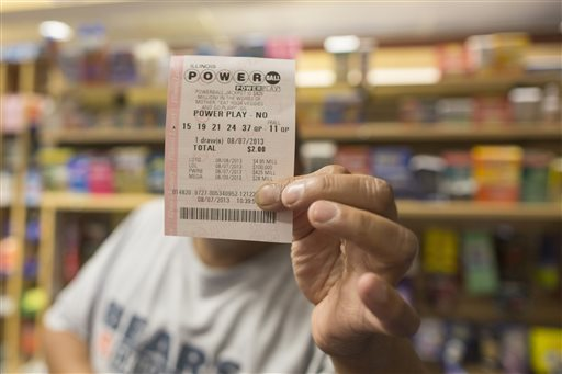 A man holds up his Powerball ticket inside of a convenience store in Chicago, Wednesday. Three tickets — one sold in Minnesota and two in New Jersey — matched Wednesday's winning numbers for a jackpot estimated at $448 million at the time of the drawing.