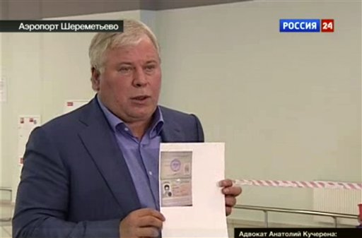 In this image taken form Russia24 TV channel, Russian lawyer Anatoly Kucherena shows a temporary document to allow Edward Snowden cross the border into Russia.