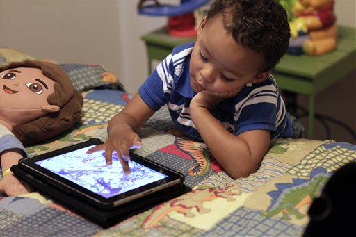 "Frankie Thevenot, 3, plays with an iPad in his bedroom at his home in Metairie, La., in this October 2011 photo. The American Academy of Pediatrics discourages any electronic ""screen time"" for infants and toddlers under age 2, while older children should be limited to one to two hours a day."
