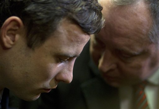 Double-amputee Olympian Oscar Pistorius, left, talks with his lawyer, Kenny Oldwage, at the magistrates court in Pretoria, South Africa, on Monday. Pistorius was indicted on charges of murder and illegal possession of ammunition for the shooting death of his girlfriend on Valentine's Day.