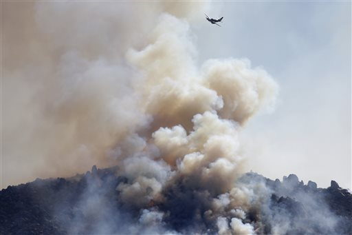 A small plane flies over a wildfire burning near Banning, Calif., on Thursday. About 1,500 people have fled and three have been injured as a wildfire in the Southern California mountains quickly spreads. Several small communities have evacuated.