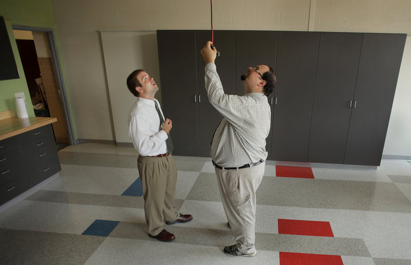 Jonathan Whitehead, left, an engineering teacher at Thornton Academy, and fellow Physics teacher Matthew Amoroso, at right, test out the drop extension cords in the school's new STEM lab, unveiled Wednesday, August 21, 2013.