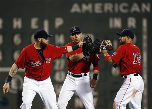 Boston Red Sox outfielders Jonny Gomes, left, Jacoby Ellsbury and Shane Victorino (18) celebrate after defeating the Chicago White Sox 4-3 in a baseball game at Fenway Park in Boston, Friday, Aug. 30, 2013. (AP Photo/Elise Amendola)