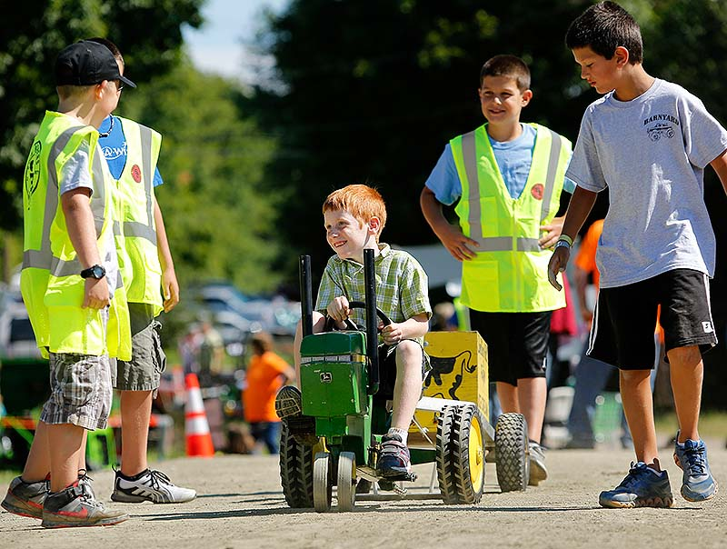Owen WInslow of Auburn, who had brain surgery nine weeks ago, pedals a tractor as the Southern Maine Garden Tractor Pulling Club holds its 6th annual fundraiser for the Make-A-Wish Foundation in Saco on Sunday.