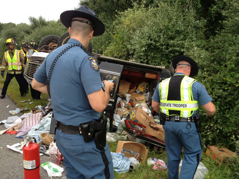 State police troopers John Lacoste, left, and Dane Wing, right, examine the scene of a single-vehicle rollover at Interstate 95 exit 112A in Augusta today. One person was dead in the crash, according to Trooper Dane Wing. Augusta Fire Department Lt. Jason Farris is seen in background, left.