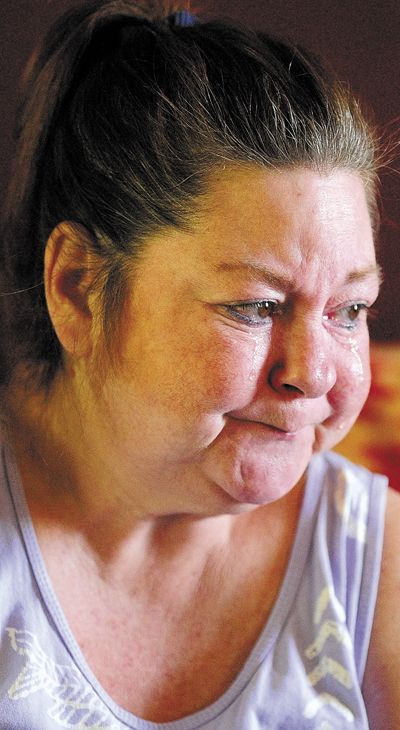Pamela Tardiff cries while telling the story of her frustrations with the new ride scheduling system on Friday in Augusta. Tardiff uses an powered wheelchair and has had trouble getting rides to doctors appointments.