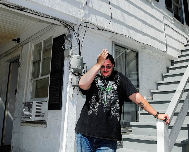 "William Thorp puts his hand to his head while discussing have to move on short notice today at 9 Laurel St. in Augusta. The city ordered the nine residents of the building out by 3 p.m. today, citing ""significant Life Safety Code deficiencies and some structural problems with the exterior porches and stairs."""