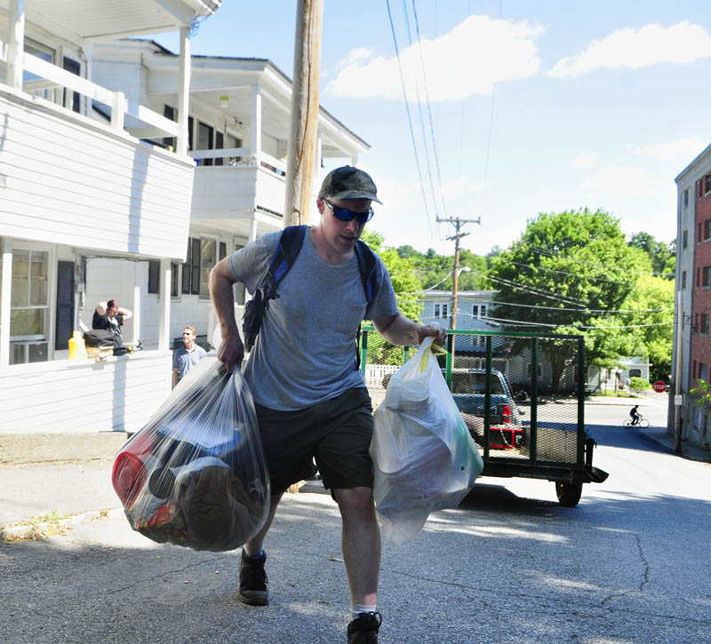 Peter Coltart carries bags of belonging towards a taxi as he moves out today at 9 Laurel St. in Augusta.