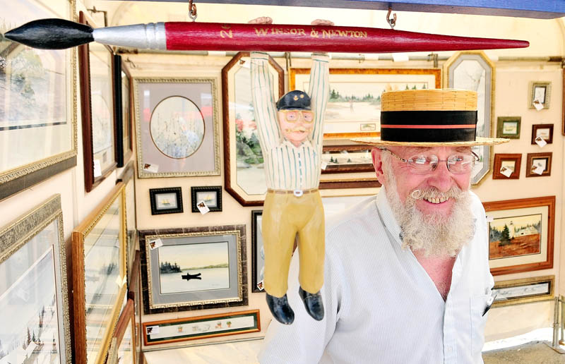 Artist Marvin Jacobs stands in his booth at the 26th annual Winthrop Sidewalk Art Show today in downtown Winthrop.