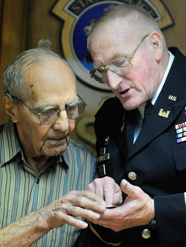 World War II veteran Al Kramer, of South China, left, and Peter W. Ogden, Director of the state's Bureau of Veterans' Services, look at a commemorative coin given to Kramer during a ceremony on Thursday in Augusta.