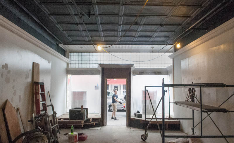 Ian Pillsbury is framed in the doorway during renovation work at the new location of LIsa's Legit Burritos, today on Water Street in downtown Augusta. As part of the renovation work the dropped tile ceiling was removed to expose the ornated metal ceiling and upper front windows.