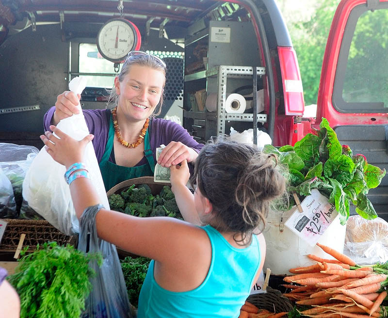 Sarah Smith, of Grassland Organic Farm in Skowhegan, left, sells beans to Shania Willette, 11 of Chelsea, on Tuesday at the Farmers Market in Mill Park in Augusta.