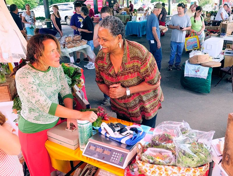 Farmer Dalziel Lewis, left, chats with customer Gloria Payne, of Augusta, at the Dig Deep Farm booth on Tuesday at the Farmers Market in Mill Park in Augusta.