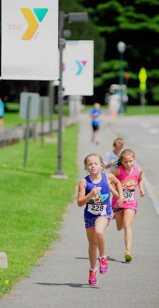 Kristen Kirk, left, and Grace Kirk sprint for the finish line during the youth division race of the Capital Y Tri today in Augusta. Grace Kirk won the 8-to-9-year-old girls division with a time of 15:50.1, edging out Kristen Kirk, at 15:50.4.
