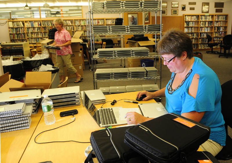 Melissa Gregoire puts an Apple MacBook Air into a carrying case on Wednesday at Gardiner Area High School in Gardiner. Gregoire and other workers were preparing the 732 new laptops that will issued to all students and staff at the high school for the coming school year.