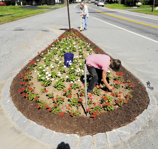 Bill Meyer, top, and Winter Webb clean up and weed a traffic island on Friday in Belgrade Lakes. Meyer said they had been weeding and sweeping around the island every Friday this summer.