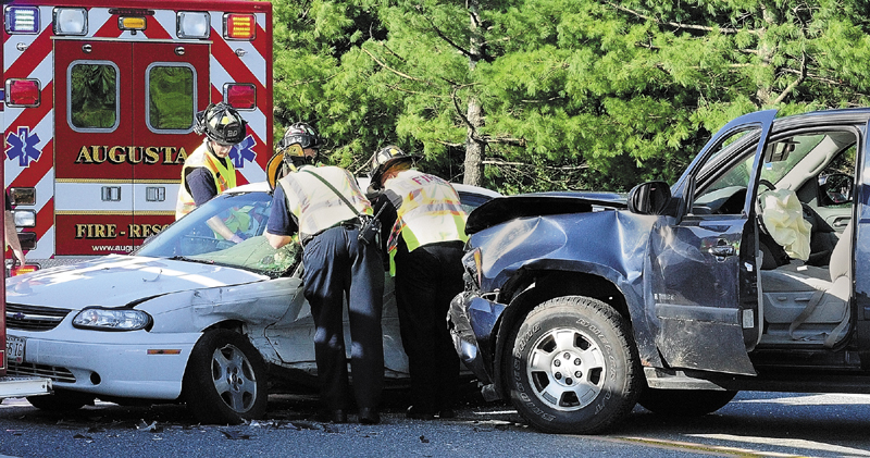 Augusta firefighters work to remove the driver of a passenger car that was struck broad side by an SUV around 5 p.m. on Wednesday in the intersection of Xavier Loop and Civic Center Drive near the entrance to Marketplace At Augusta.