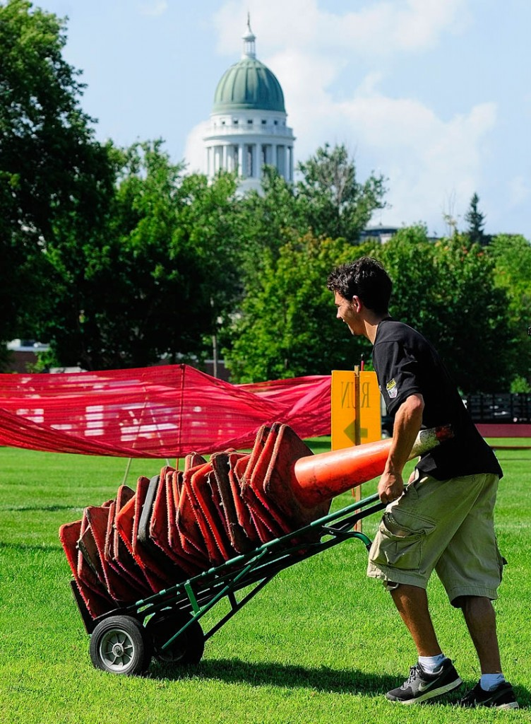 Curtis Coleman rolls cones into position today as the crew from All Sports Events sets up the transition and finish area for the Capital Y Tri , between the Kennebec Valley YMCA and the State House in Augusta. The inaugural event starts at 7 a.m. Saturday for adult competitors, followed by a children's triathlon. Adults will swim 425 yards in the pool, then bike 11 miles before finishing with a 3.1 mile run.
